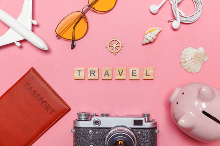 Vacation travel summer weekend adventure trip concept. Minimal simple flat lay with plane vintage camera passport sunglasses piggy bank and shell on pink pastel trendy background. Tourist essentials