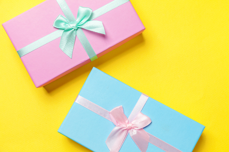 Christmas New Year birthday valentine celebration present romantic concept. Gift box wrapped blue pink paper isolated on yellow colourful trendy modern fashion background. Flat lay top view copy space