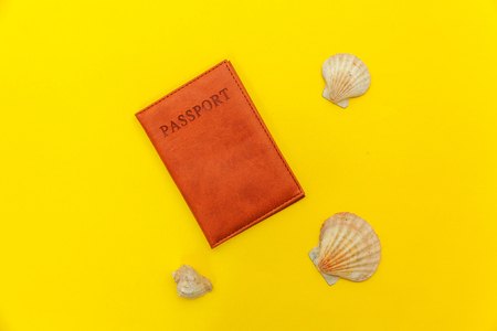 Travel vacation summer weekend sea adventure trip journey ticket tour concept. Minimal simple flat lay with passport and shell on yellow trendy modern background. Tourist essentials