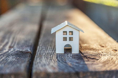 Miniature white toy model house in wooden background. Eco Village, abstract environmental background. Real estate mortgage property insurance dream home ecology concept