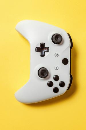 Weißes Joystick-Gamepad, Spielkonsole auf gelbem, buntem, trendigem, modernem Pin-up-Hintergrund. Konfrontationskonzept für Computerspiele-Wettbewerbs-Videospiele. Cyberspace-Symbol