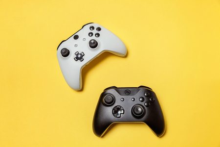 White and black two joystick gamepad, game console on yellow colourful trendy modern fashion pin-up background. Computer gaming competition videogame control confrontation concept. Cyberspace symbol 스톡 콘텐츠