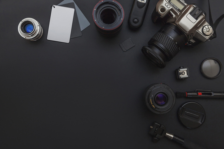 Photographer workplace with dslr camera system, camera cleaning kit, lens and camera accessory on dark black table background. Hobby travel photography concept. Flat lay top view copy space Stockfoto