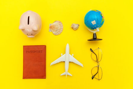 Vacation travel adventure trip concept. Minimal simple flat lay with plane passport sunglasses globe piggy bank sleeping eye mask and shell on yellow colourful trendy background. Tourist essentials