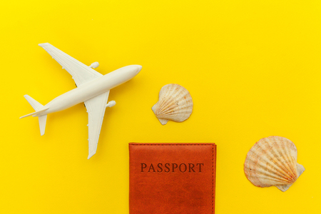 Travel by plane vacation summer weekend sea adventure trip journey ticket tour concept. Minimal simple flat lay with plane shell and passport on yellow trendy modern background. Tourist essentials