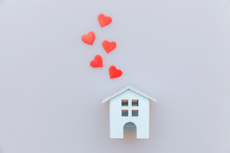 Simply minimal design with miniature white toy house and red heart isolated on white background. Mortgage property insurance dream home concept. Flat lay top view copy space 스톡 콘텐츠