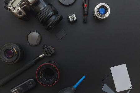 Photographer workplace with dslr camera system, camera cleaning kit, lens and camera accessory on dark black table background. Hobby travel photography concept. Flat lay top view copy space Stock fotó