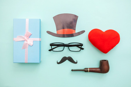 Happy Father's day concept. Sign of hat mustache with pipe glasses red heart gift box isolated on pastel blue background. Simple minimalism flat lay top view copy space. Man silhouette symbol