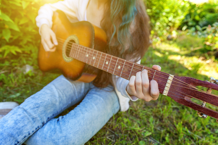 Closeup of woman hands playing acoustic guitar on park or garden background. Teen girl learning to play song and writing music. Hobby, lifestyle, relax, Instrument, leisure, education concept Standard-Bild