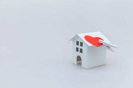 Simply minimal design with miniature white toy house and red heart isolated on white background. Mortgage property insurance dream home concept. Copy space
