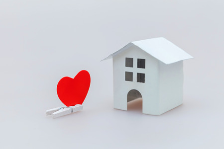 Simply minimal design with miniature white toy house and red heart isolated on white background. Mortgage property insurance dream home concept. Copy space Reklamní fotografie