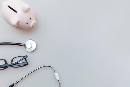 Gafas de hucha con estetoscopio o fonendoscopio de equipo médico de medicina aisladas sobre fondo blanco. Chequeo financiero de atención médica o ahorro para el concepto de costos de seguro médico Foto de archivo