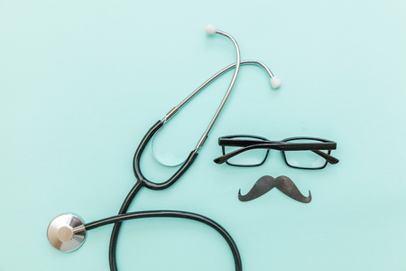 Man health care concept. Simply minimal design with medicine equipment stethoscope or phonendoscope glasses sign of mustache isolated on trendy pastel blue background. Doctor urologist Stock Photo