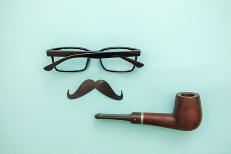 Happy Fathers day concept. Sign of mustache with pipe glasses isolated on pastel blue background. Simple minimalism flat lay top view copy space. Man silhouette symbol Stok Fotoğraf