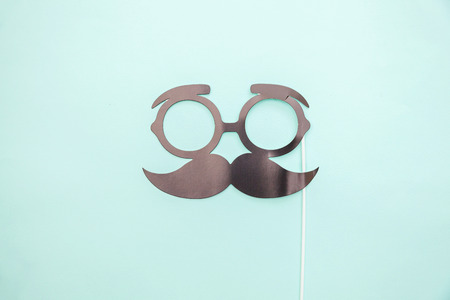 Happy Fathers day concept. Sign of mustache with glasses isolated on pastel blue background. Simple minimalism flat lay top view copy space. Man silhouette symbol