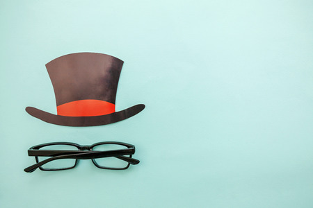 Happy Fathers day concept. Sign of hat with glasses isolated on pastel blue background. Simple minimalism flat lay top view copy space. Man silhouette symbol Stok Fotoğraf