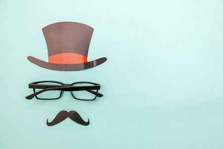 Happy Fathers day concept. Sign of hat mustache with glasses isolated on pastel blue background. Simple minimalism flat lay top view copy space. Man silhouette symbol Stok Fotoğraf