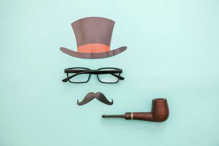 Happy Fathers day concept. Sign of hat mustache with pipe glasses isolated on pastel blue background. Simple minimalism flat lay top view copy space. Man silhouette symbol