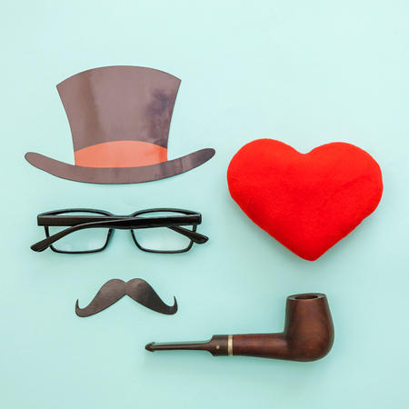 Happy Fathers day concept. Sign of hat mustache with pipe glasses red heart isolated on pastel blue background. Simple minimalism flat lay top view copy space. Man silhouette symbol