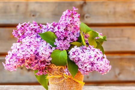 Concepto de primavera de naturaleza ecología. Ramo de flores hermoso olor violeta violeta lila en florero sobre fondo de madera rústica. Jardín o parque floreciente de la primavera floral natural inspirador