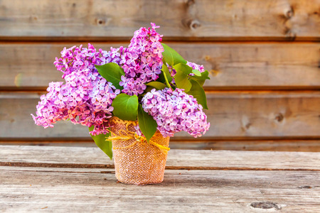 Ecology nature springtime concept. Bouquet of flowers beautiful smell violet purple lilac in vase on rustic wooden background. Inspirational natural floral spring blooming garden or park
