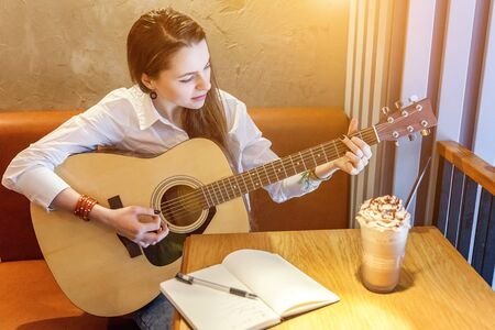 Young hipster woman sitting at table and playing guitar in cafe background. Teen girl learning to play song and writing music. Hobby, lifestyle, relax, Instrument, leisure, education concept