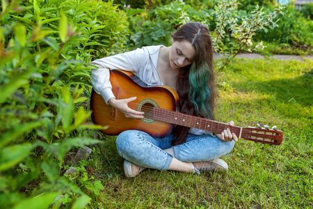 Young hipster woman sitting in grass and playing guitar on park or garden background. Teen girl learning to play song and writing music. Hobby, lifestyle, relax, Instrument, leisure, education concept Reklamní fotografie - 133850535