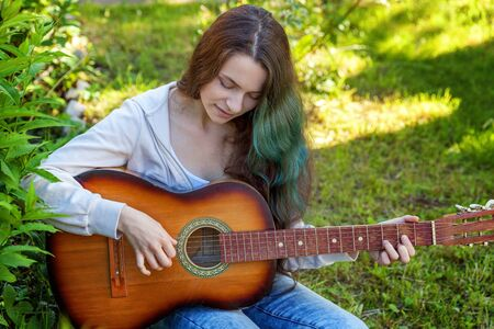Young hipster woman sitting in grass and playing guitar on park or garden background. Teen girl learning to play song and writing music. Hobby, lifestyle, relax, Instrument, leisure, education concept Reklamní fotografie - 133850564