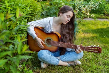 Young hipster woman sitting in grass and playing guitar on park or garden background. Teen girl learning to play song and writing music. Hobby, lifestyle, relax, Instrument, leisure, education concept Reklamní fotografie - 133850614