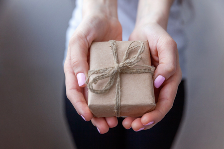 Female hands holding small gift box wrapped craft paper with ribbon. Small christmas or new year decorated gift in the hands of woman. Christmas birthday valentine celebration present romantic concept