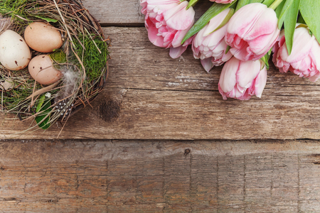 Spring greeting card. Easter eggs in nest with moss and pink fresh tulip flowers bouquet on rustic shabby wooden background. Easter concept. Flat lay top view copy space. Spring flowers tulips 版權商用圖片