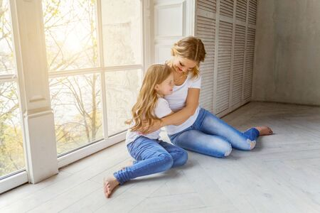 Mother hugging child. Woman and girl relax and playing in bedroom near windiow. Happy family at home. Mom playing with her daughter. Family, maternity, tenderness, parenthood, responsibility concept Reklamní fotografie - 133850628