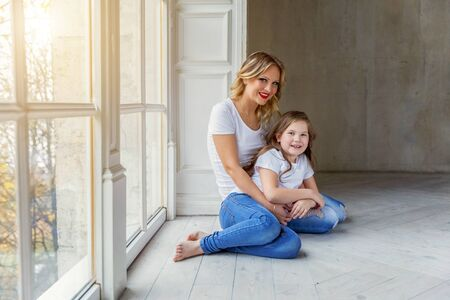Mother hugging child. Woman and girl relax and playing in bedroom near windiow. Happy family at home. Mom playing with her daughter. Family, maternity, tenderness, parenthood, responsibility concept Reklamní fotografie - 133850981