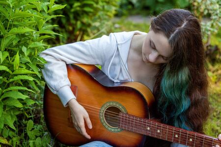 Young hipster woman sitting in grass and playing guitar on park or garden background. Teen girl learning to play song and writing music. Hobby, lifestyle, relax, Instrument, leisure, education concept 스톡 콘텐츠