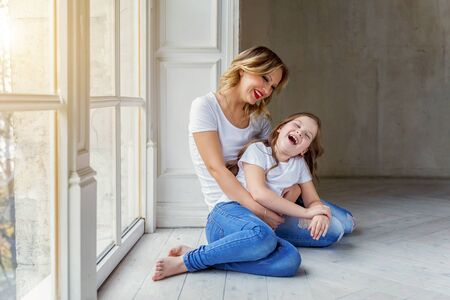 Mother hugging child. Woman and girl relax and playing in bedroom near windiow. Happy family at home. Mom playing with her daughter. Family, maternity, tenderness, parenthood, responsibility concept