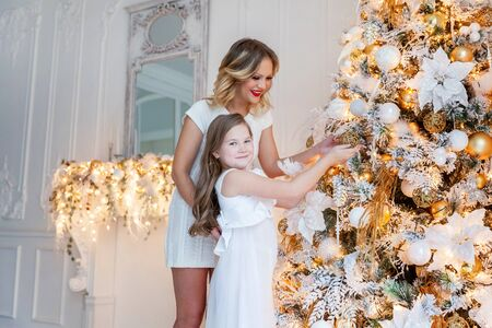 Happy family mother and daughter decorating a Christmas tree on Christmas eve at home. Woman and little girl relax in a white bedroom near the Christmas tree. Family at home. Young mother playing whith her daughter