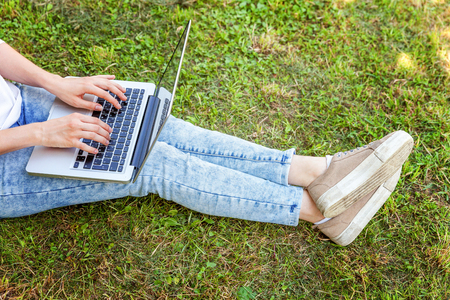 Freelance business concept. Woman legs on green grass lawn in city park, hands working on laptop pc computer. Lifestyle authentic candid student girl studying outdoors. Mobile Office Imagens