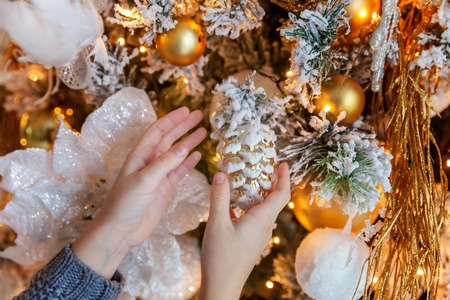 Little girl decorating Christmas tree on Christmas eve at home. Young kid in light bedroom with winter decoration. Christmas New Year december time for celebration concept Imagens