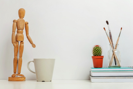 Home or office decor with mannequin coffee cup near white wall. Minimalism interior workplace artist supplies decoration background. Hygge scandinavian style workspace concept. Copy space mock up