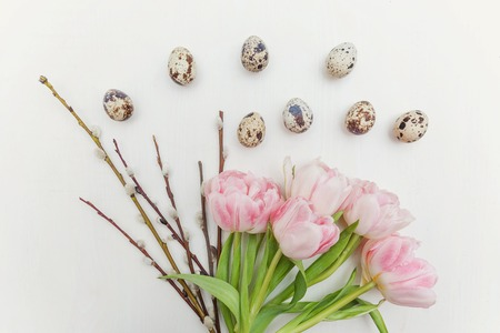Spring greeting card. Easter eggs cotton willow branch and pink fresh tulip flowers bouquet on rustic white wooden background. Easter concept. Flat lay top view copy space. Spring flowers tulips Imagens