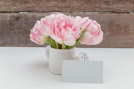 Spring greeting card. Bouquet of fresh light pastel pink tulips flowers small toy watering can vase on rustic wooden background. Happy holiday mother day valentine day concept. Flat lay top view copy space Imagens