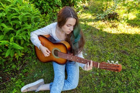 Young hipster woman sitting in grass and playing guitar on park or garden background. Teen girl learning to play song and writing music. Hobby, lifestyle, relax, Instrument, leisure, education concept Reklamní fotografie