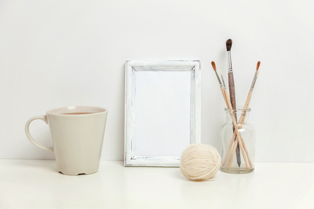 Vertical frame mockup with coffee cup near white wall. Empty frame mock up for presentation design. Template framing for modern art. Hygge scandinavian style workspace. Natural eco home decor Imagens