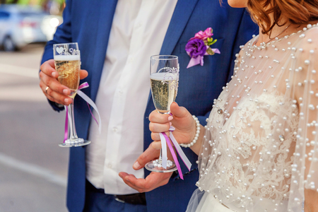 Wedding selebration. Bride and groom holding glasses of champagne making a toast, hands with glasses close up