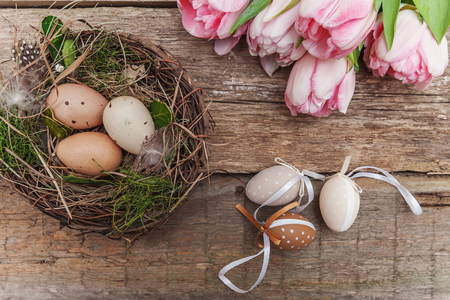 Spring greeting card. Easter eggs in nest with moss and pink fresh tulip flowers bouquet on rustic shabby wooden background. Easter concept. Flat lay top view copy space. Spring flowers tulips Imagens