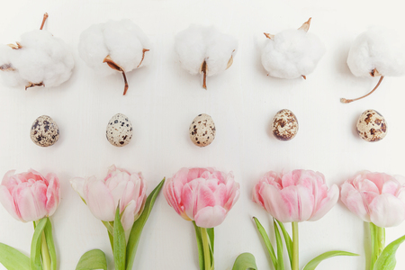 Spring greeting card. Easter eggs cotton and pink fresh tulip flowers bouquet on rustic white wooden background. Easter concept. Flat lay top view copy space. Spring flowers tulips Imagens