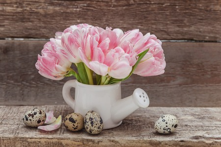 Spring greeting card. Easter eggs pink fresh tulip flowers bouquet small toy watering can vase on rustic shabby wooden background. Easter concept. Copy space. Spring flowers tulips