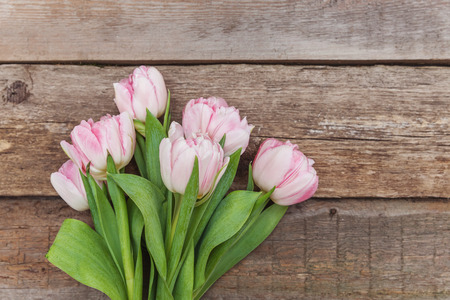 Spring greeting card. Bouquet of fresh light pastel pink tulips flowers on wooden background. Happy holiday easter mother day anniversary valentine day birthday concept. Flat lay top view copy space