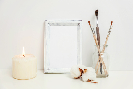 Vertical frame mockup with candle brush vase near white wall. Empty frame mock up for presentation design. Template framing for modern art. Hygge scandinavian style workspace. Natural eco home decor Standard-Bild