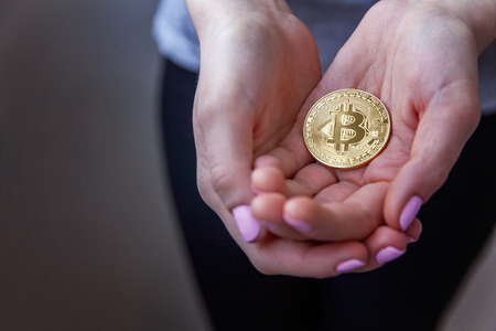 Cryptocurrency golden bitcoin coin in woman hand. Electronic virtual money for web banking and international network payment. Symbol of crypto currency Imagens